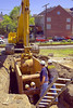 Earthmoving/ trenching construction, safety: Caterpillar 320CL track mounted hydraulic excavator/backhoe excavates a bucket of soil inside trench shield/box. Trench shield extends from bottom of trench to above top of excavation and protects the workers inside it from possible trench wall cavein. Backhoe bucket is sized to fit interior width of shield. Primary excation was by this same backhoe using a wider, larger bucket. Bucket has picked up soil from bottom and is now raising it up to dump into excavation outside the shield. First Street, Ann Arbor, Michigan 2006.