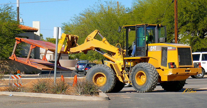 Trench construction/safety: Caterpillar 938G articulated wheeled tractor with forklift attachment transports steel trench box/shield from one position to another along a trench. Tucson, Arizona November 2006.