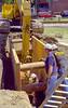 Earthmoving/ trenching construction, safety: Caterpillar 320CL track mounted hydraulic excavator/backhoe excavates a bucket of soil inside trench shield/box. Trench shield extends from bottom of trench to above top of excavation and protects the workers inside it from possible trench wall cavein. Backhoe bucket is sized to fit interior width of shield. Primary excation was by this same backhoe using a wider, larger bucket. First Street, Ann Arbor, Michigan 2006.