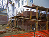 "Masonry construction, construction safety: Manufactured tubular scaffold posts supported at base by unstable brick cribbing. Preferred methods would include screw-jacks at scaffold bases extended to stable mud sill or other stable footing. 2"" x 10"" wood planks form working platform for masons to stand on and a higher material platform on which masonry units (brick here) and mortar are placed. The outside of the material level should have guardrails to protect laborers placing and stacking brick and working with mortar. The ramp between the side and front sections of scaffold should also have guardrails and also cleats for good footing, especially in the wet weather in which masons are working. Ann Arbor, Michigan, 2004<br />     OSHA 1926-L requires: Supported scaffold poles, legs, posts, frames, and uprights shall bear on base plates and mud sills or other adequate firm foundation. Footings shall be level, sound, rigid, and capable of supporting the loaded scaffold without settling or displacement. Unstable objects shall not be used to support scaffolds or platform units."