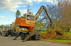 Landscape construction, debris removal: Barko trailer mounted hydraulic boom forestry loader picking up tree debris after Hurricane Wilma. Naples, Florida November 2005.<br /> Electrical construction, personnel lifts: Two electric utility crews use hydraulic boom cherry picker personnel lifts on service trucks to repair lines at the blinking light, Pepperell, Massachusetts, 2005<br /> Bridge construction, steel construction: Erecting prefabricated panels of a Mabey steel truss panel temporary bridge over the Merrimac River on Route 113. Ironworker on top of erected panels guides crane operator, facing toward us, while ground man guides panel into place. Panels are connected by single driven pin at bottom and bolted connection at top. Tyngsborough, MA 2005.