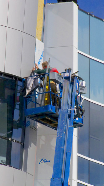 Cladding installation/construction: Two workers in Genie S65 hydraulic telescoping boom elevated work platform install panel of custom curved Reynobond composite cladding on sloped façade of building. Composite cladding is a sandwich of inside and outside layers of metal that enclose rigid insulation. Depot Street, Ann Arbor, Michigan, December 2006.