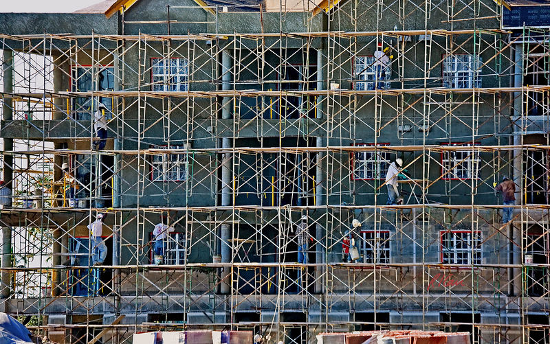 Building construction, stucco: Large crew applies stucco (exterior plaster) over concrete block walls of multistory residential building. Scaffold is welded tube modular scaffold sections that fit together and provide steps at 2' o.c. for workers to climb, as at midheight right. Stucco is mixed on ground in a mixer and hoisted onto scaffold by rope (across middle of picture) and pulley. A worker is pulling stucco bucket onto scaffold planking in middle right of picture. Stucco has been applied near top, and crew is working on different portions at different levels. Fall protection is provided, loosely, by cross bracing and by tubing passed through the lowest step of outside scaffold ladder, though this in incomplete. Ft. Myer Beach, November 2005.