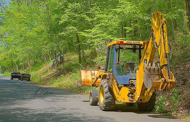 Landscape construction, tree planting: John Deere 210C backhoe loader and Jacobsen tilt bed utility trucks support workers planting balled root trees on side of hill. Backhoe loader carries trees, and utility trucks transport workers, tools, and any soil required. Radrick Farms Golf Course, University of Michigan, Ann Arbor, May 2006.