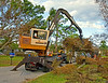Landscape construction, debris removal: Barko trailer mounted hydraulic boom forestry loader, with outriggers/load stabilizers extended, picking up tree debris after Hurricane Wilma. Naples, Florida November 2005.<br /> Electrical construction, personnel lifts: Two electric utility crews use hydraulic boom cherry picker personnel lifts on service trucks to repair lines at the blinking light, Pepperell, Massachusetts, 2005<br /> Bridge construction, steel construction: Erecting prefabricated panels of a Mabey steel truss panel temporary bridge over the Merrimac River on Route 113. Ironworker on top of erected panels guides crane operator, facing toward us, while ground man guides panel into place. Panels are connected by single driven pin at bottom and bolted connection at top. Tyngsborough, MA 2005.