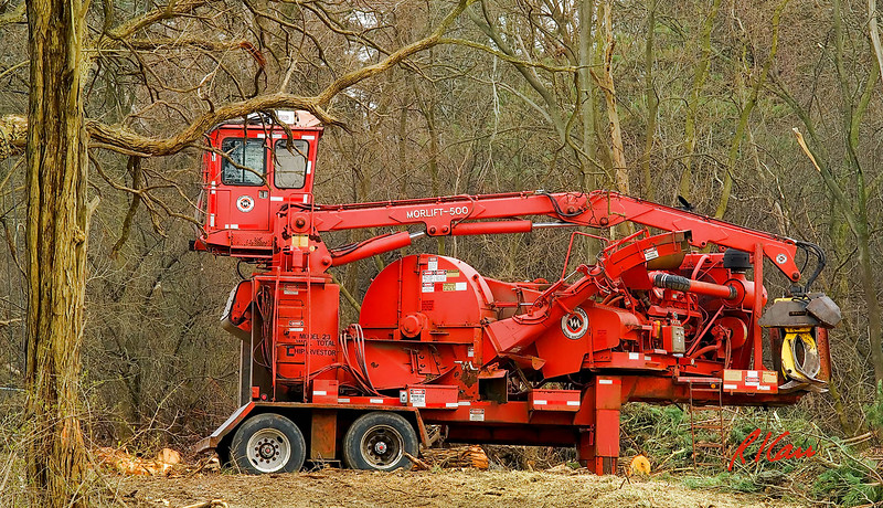 Morbark Model 23 Total Chiparvestor produces wood chips from whole logs. Operator in cab at top operates entire machine including its Morlift 500 Knuckleboom Loader, which is a hydraulic boom crane, that picks up logs with it grappler and feeds them into the Model 23 75 inch chipper to produce a variety of outputs, from pulp to wood chips. Knuckleboom loader has 23 ft reach and lift capacity of 17,200 lb at 10 ft. Ann Arbor, Michigan, April 2007.