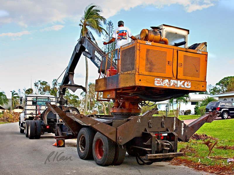 Landscape construction, debris removal: Barko trailer mounted hydraulic boom forestry loader preparing to move. Outriggers/load stabilizers are being lifted for travel, boom is extending to rest on trailer yoke, and tractor will pull it to another position. Naples, Florida November 2005.