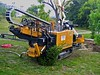 Underground construction: Vermeer D80x120 Navigator horizontal directional drill (HDD) engine in rear driving drill stem into mud hole drilling horizontally next to intramural athletic fields. In background is white truck mounted crane. University of Michigan, Ann Arbor, 2004.