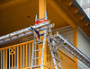 Residential/frame construction: Aluminum extension ladders, ladder jacks, and picks/planks/stages provide makeshift scaffolding for exterior construction of wood frame residence. Body harnesses, lanyards, and safety lines/ tie-offs should be used to provide fall protection for workers on the picks/planks/stages. Route 30A, Panhandle, Florida 2006.