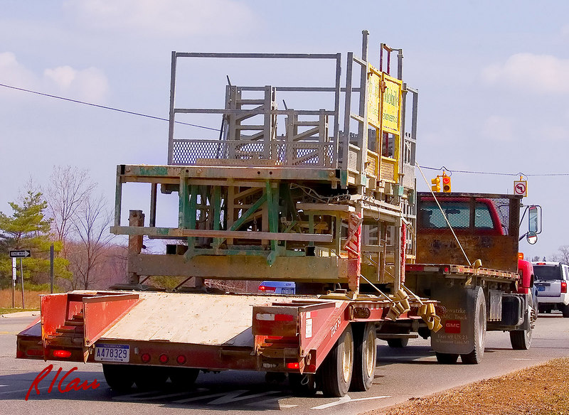 Hydro-Mobile self-elevating masonry scaffold stacked and strapped on low-boy trailer and transported between construction sites, pulled by GMC flatbed truck. Plymouth Road at US23, Ann Arbor, Michigan. March 2007