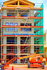 Construction, tubular scaffold, manlift: Tubular steel scaffold on front of building is accessed using ladders between levels and holes in work platforms/stages. JLG 600AJ hydraulic telescoping boom man-lift is parked in front of building. Green plastidc screen protects adjoining building to right. Reinforced concrete structure commercial building at central square of the town of WaterColor, Florida Panhandle, June 2006.