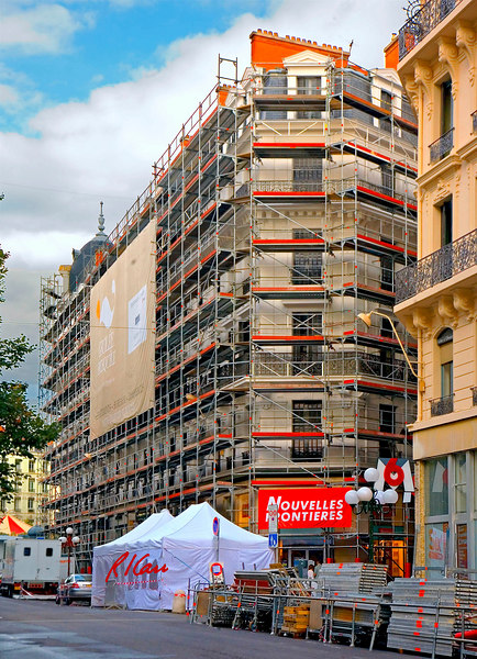 Construction scaffold/platform: Tubular scaffold supports work platforms for renovating exterior of multistory building with stucco/plaster/ wrought iron exterior/ decoration. Additional scaffold components are stored in street. Lyon, France September 2006