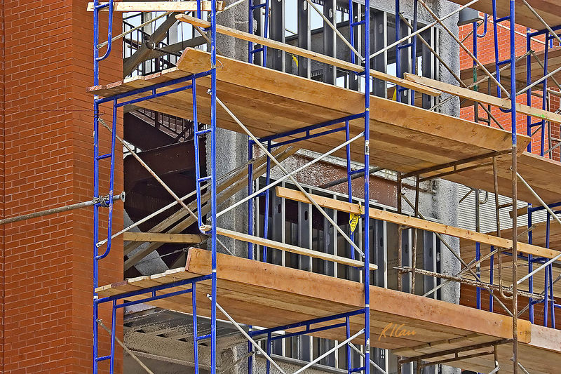 """Construction scaffold: Welded steel tubular modular scaffold with 2""""x10"""" wood plank platforms and toe-boards. 2""""x4"""" lumber guardrails inserted into slots in integral ladders, in conjunction with steel tube cross-bracing provide some, though not adequate, fall protection. Interior structural steel has been sprayed with fireproofing insulation. Cold-formed sheet metal studs will provide support for wall cladding. Ann Arbor, Michigan 2005."""