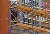 "Construction scaffold: Welded steel tubular modular scaffold with 2""x10"" wood plank platforms and toe-boards. 2""x4"" lumber guardrails inserted into slots in integral ladders, in conjunction with steel tube cross-bracing provide some, though not adequate, fall protection. Interior structural steel has been sprayed with fireproofing insulation. Cold-formed sheet metal studs will provide support for wall cladding. Ann Arbor, Michigan 2005."