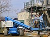 Building construction: Genie rough terrain telescoping boom man lift. Hydro-Mobile mast-climbing work platform is at back right . Delonis Shelter, Ann Arbor.