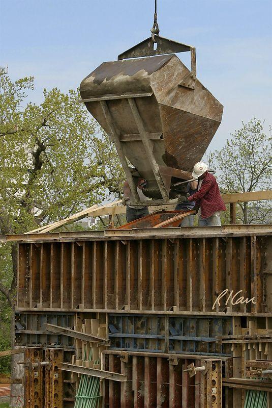 Concrete construction: Laborers align crane supported laydown type concrete bucket. They will open its bottom gate to place concrete in bridge pier. Orange hopper funnels concrete into pier. Broadway Bridge, Ann Arbor, 2003.
