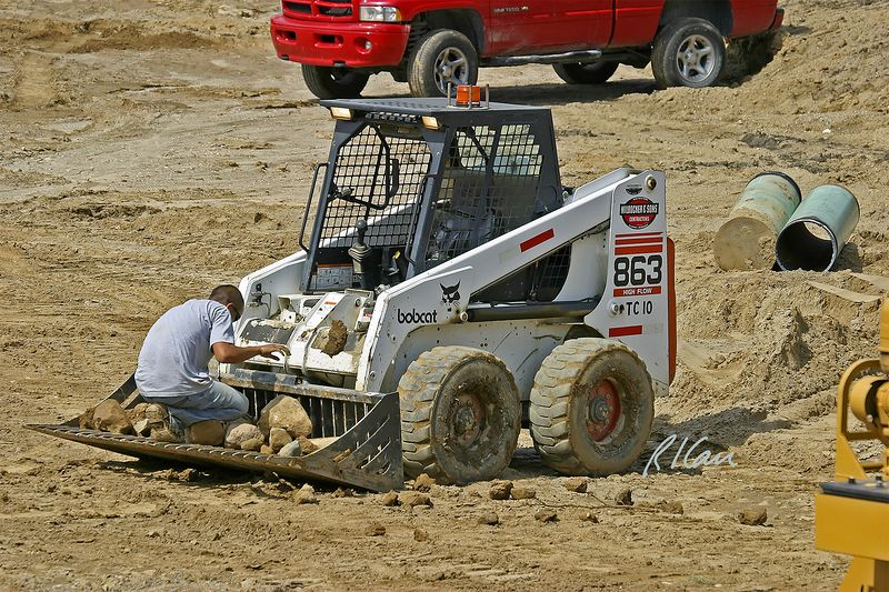Earth moving construction: Bobcat 863 skid-steer tractor with stone separating blade/bucket lifts and sifts soil to extract and separate stones. Operator is picking out and tossing away soil clumps that sifted out with stones. Dixboro Bridge, Ann Arbor, MI, 2004.