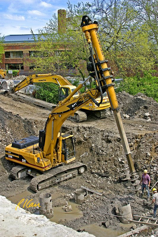Underground construction: Rohrscheib earth auger mounted on Caterpillar 330B crawler mounted hydraulic backhoe boom. In background is Komatsu PC300LC crawler mounted backhoe. Broadway Bridge, Ann Arbor, 2003.