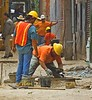 Manhole construction, sewer/drain construction, masonry construction: Worker seals/parges manhole masonry by applying mortar by hand to inside of manhole ring casting, which will support manhole cover, and manhole masonry wall. Mortar has been hand carried from the mortar mixer at entrance to this alley, in the buckets shown here. Alley between Washington and Liberty, 1/2 block West of Main, Ann Arbor, Michigan, 2005.