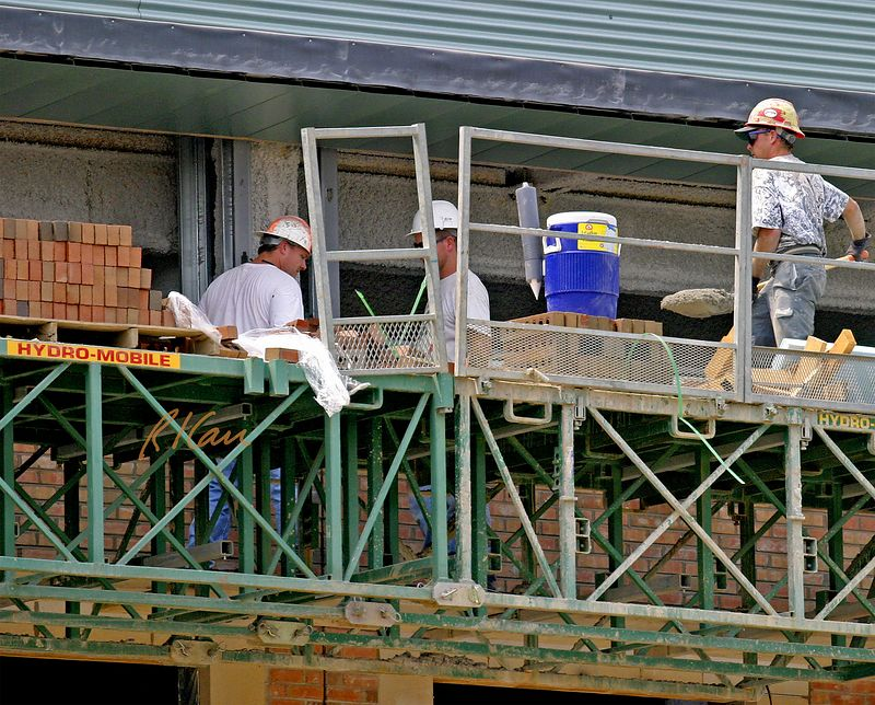 Brick construction: Laborer transporting mortar from mortar box to mortar boards of bricklayers.  Construction of YMCA, Ann Arbor, 2004.