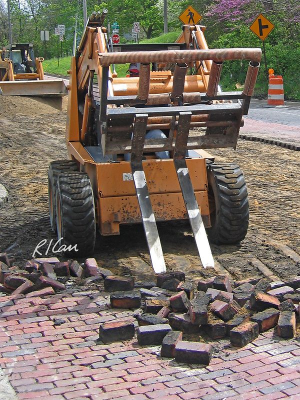 Case 1845C skid steer tractor with forklift attachment has broken loose a segment of brick paver street. Depot Street, Ann Arbor, 2004.