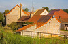 French residential/house construction: Variety of hard-baked clay tile roofs, from new to old, on neighboring houses. Central Canal, Burgundy, France September 2006.