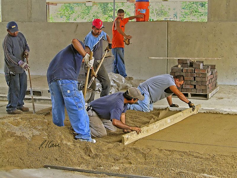 Road construction, masonry construction: Workers place sand on concrete base and hand grade sand to receive brick pavers on pallet in background. Broadway Bridge and Depot Street, Ann Arbor, 2004.