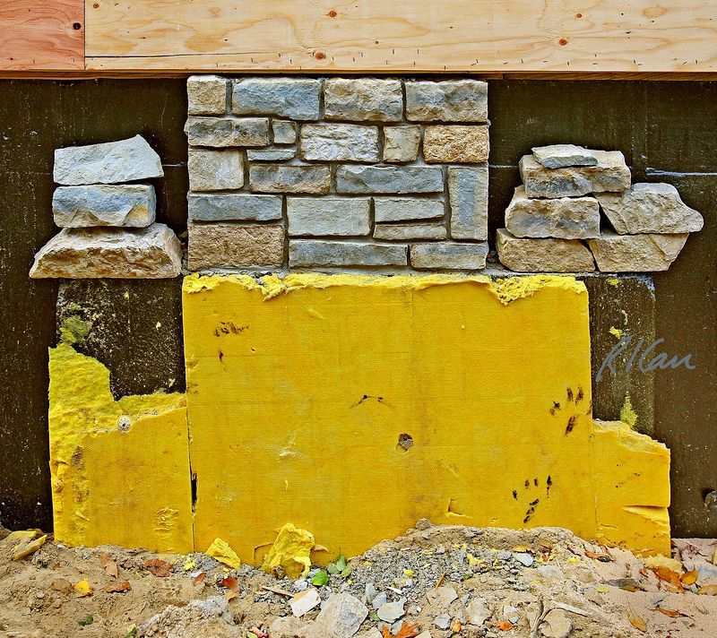 Stone/rock masonry construction: Sample for Architect's/Owner's approval of stone for wall of residence. Stone mason has laid selected stone in specified pattern, with additional stone samples, on foundation masonry ledge, for architect and/or owner to view and approve or request changes. Top of photo is 4'x8' sheets of plywood exterior sheathing, nailed to vertical studs, laid horizontally so plywood exterior laminations are perpendicular to supporting studs. Black background is bitumen layer painted on concrete basement wall to resist penetration of moisture from earth through wall. Yellow material is exterior rigid fiberglass insulation between ground and basement wall, once soil is backfilled against wall insulation.. Arlington Street, Ann Arbor, Michigan 2005.
