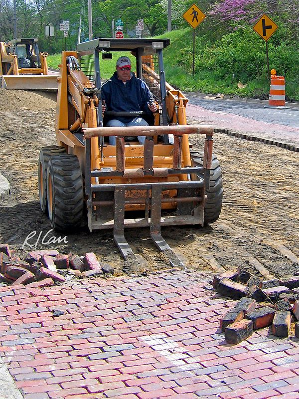 Case 1845C skid steer tractor with forklift attachment is forcing fork lift prongs under brick pavers on street. Depot Street, Ann Arbor, 2004.