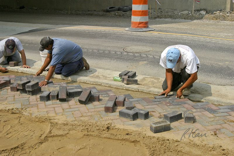 Pavement construction: Placing brick pavers in herringbone pattern on sand base for traffic ramp to bridge. Broadway Bridge and Depot Street, Ann Arbor, 2004.