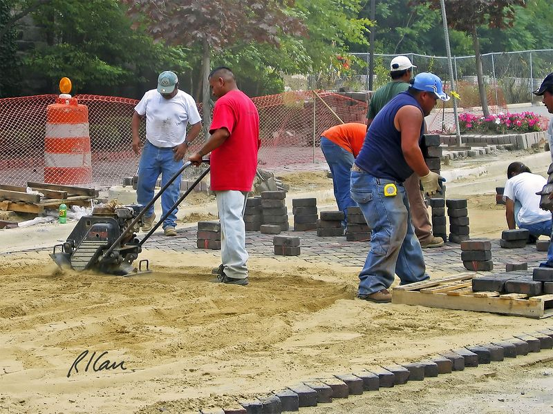 Road construction, masonry construction: Workers placing brick pavers in herringbone pattern for Depot Street under Broadway Bridge. Workers middle right carry pavers from forklift pallet to workers who are placing pavers at leading edge on sand base back right. Worker mid-left is compacting sand between pavers. About 10 feet of pavers are ready to receive sand. Ann Arbor, 2004.