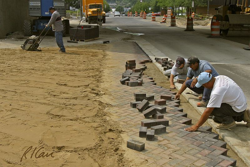 Pavement construction: Placing brick pavers in herringbone pattern for traffic ramp to bridge. Pavers are placed on sand base, then covered with sand to fill voids between bricks. Sand is compacted with vibratory compactor as shown in left rearm and the excess sand is swept off paver surface. Broadway Bridge and Depot Street, Ann Arbor, 2004.