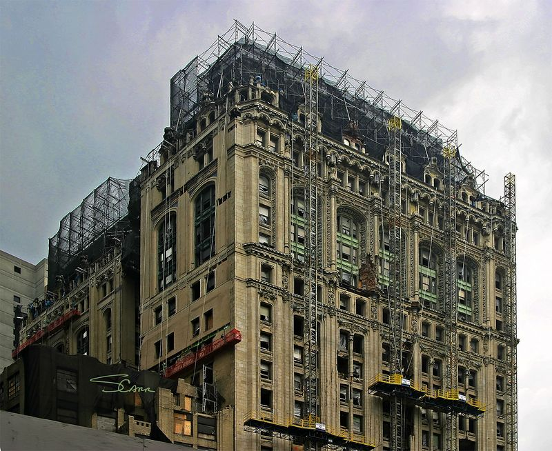 Rehab construction: Self elevating exterior scaffolds for rehabilitation of stone facade of older building. Welded scaffold at roof to rebuild roof. New York City, 2004