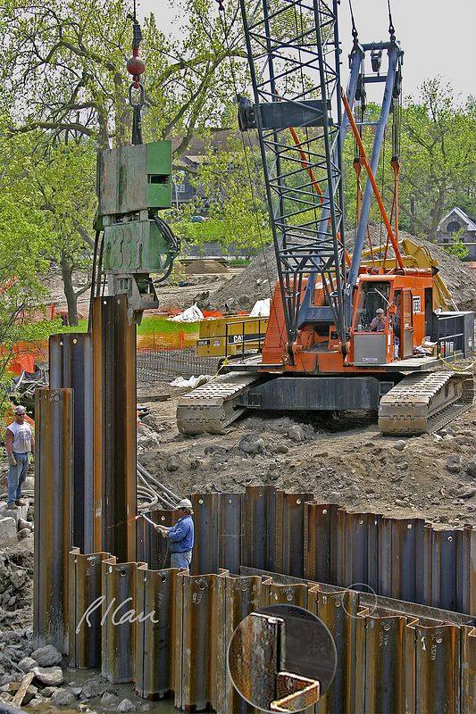 Construction pile driving: ICE 812 Vibro-Hammer vibratory pile driver/extractor drives sheet piles to form cofferdam at Huron River. Sheet pile sections are connected by interlocking edges, which allow vertical slippage during sheet pile driving. (See inset detail of circled connection in photo.) Pile driver is supported by crawler mounted cable driven open web boom crane. Worker inside cofferdam is cutting off the top of the sheet pile to the right with an acetylene torch.  Broadway Bridge, Ann Arbor, 2003.