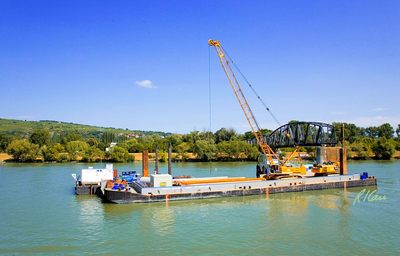 Marine/river construction: Construction barge carries Liebherr crawler mounted lattice boom, cable operated crane and ABI Mobilram pile drilling and vibratory/ impacting/ pressing rig. Barge also carries Sections of steel sheet piling to be driven to complete the cofferdam for bridge pier. Barge is controlled by construction tug. Danube River in Hungary west of Budapest, August 2006.