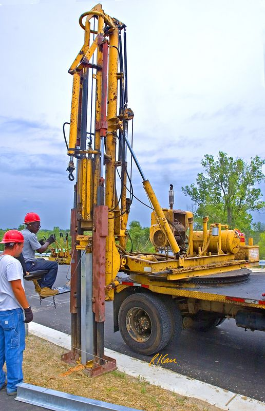 Road and fence construction: Truck mounted, highly specialized drop-hammer pile/post driver drives galvanized steel wide flange sections into ground to provide support for vehicle guardrails. Operator uses control levers to initiate lift of drop-hammer by cable and then its drop onto post/pile cap. Dixboro Bridge construction, Ann Arbor, Michigan, August 2005.