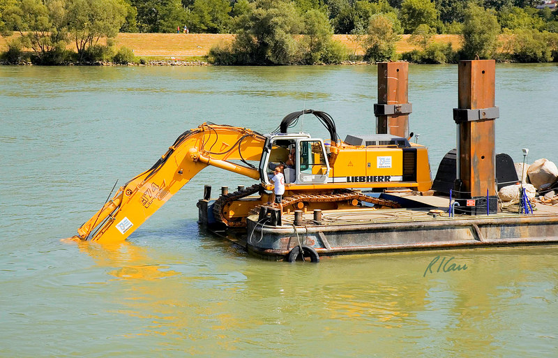 Marine/river construction: Construction barge carries Liebherr 974 Litronic hydraulic operated crawler mounted backhoe set up as an underwater dredge to shape river bottom for bridge construction. Barge is anchored by rectangular steel piers pushed a shallow distance into river bed. Danube River in Hungary west of Budapest, August 2006.