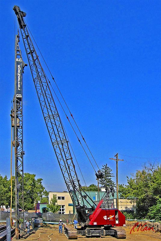 Construction pile driving: Vulcan 505 25,000 ft-lb 60 inch stroke single-acting air-driven air/steam hammer drives structural steel H piles into the ground. Piles are supported and guided by swinging leads which are supported by Manitowoc 2900WC crawler mounted open web boom cable operated crane. Delonis Shelter, Ann Arbor, 2003.