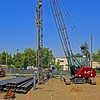 "Construction pile driving: Vulcan single-acting air-driven hammer drives structural steel H piles into the ground. Previously driven pile is seen to this side of pile driving position, labeled ""687"". H piles to be driven are to the left. Compressed air hose to power the pile hammer is shown in foreground and going up to hammer. Piles are supported and guided by swinging leads which are supported by Manitowoc 2900WC crawler mounted open web boom cable operated crane. Delonis Shelter, Ann Arbor, 2003."