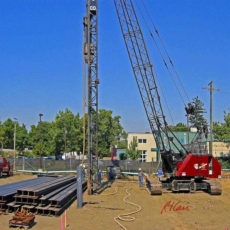 """Construction pile driving: Vulcan single-acting air-driven hammer drives structural steel H piles into the ground. Previously driven pile is seen to this side of pile driving position, labeled """"687"""". H piles to be driven are to the left. Compressed air hose to power the pile hammer is shown in foreground and going up to hammer. Piles are supported and guided by swinging leads which are supported by Manitowoc 2900WC crawler mounted open web boom cable operated crane. Delonis Shelter, Ann Arbor, 2003."""