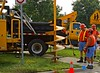 Road construction: Soil auger mounted on City truck crane boom drills a hole, at spot marked with orange paint, for pier to support lighting/sign. At auger bit full depth, boom lifts out auger after drilling to its depth, retaining a large part of the soil on the auger bit. City workers then shovel back the soil from hole to keep it from falling into the hole. Soil on bit will soon be placed in bed of truck on photo's right. Note truck crane outriggers  are extended to support crane boom against overturning the truck.Huron Parkway at Huron High School, near Huron River, Ann Arbor, MI, 2005