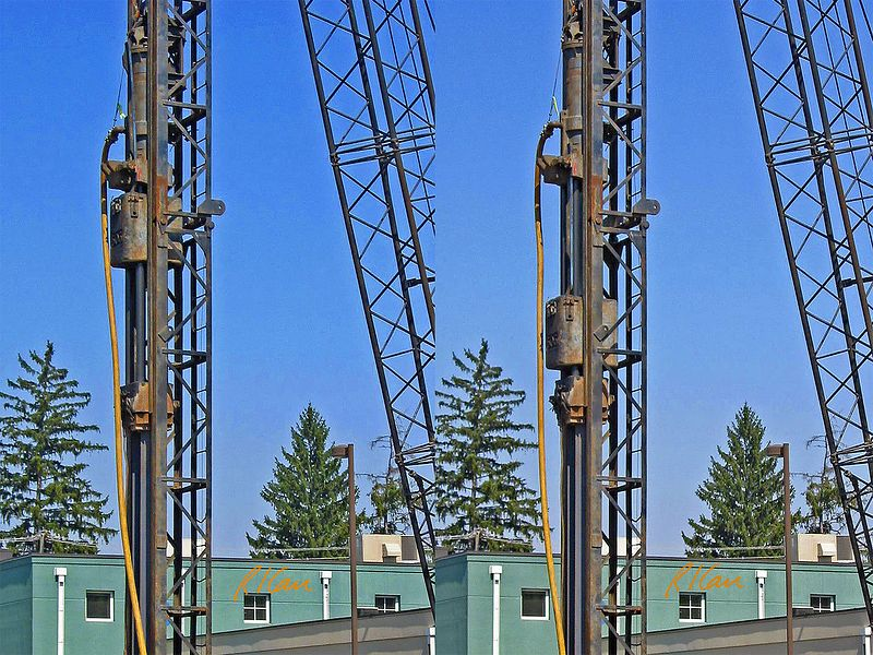 """Construction pile driving: Vulcan 505 25,000 ft-lb 60 inch stroke single-acting air-driven air/steam hammer drives structural steel H pile into the ground. The ram, marked """"505"""", is attached to the piston of the cylinder at the top of the figure. On each cycle, the cylinder raises the piston and ram to the top of the cylinder with compressed air received through the vertical compressed air hose to the left of ram. When the piston reaches the top of the cylinder (left figure), the piston and ram are released and drops/falls by gravity to impact the top of the pile (right figure), through a pile cap that protects the top of the H pile below it. Piles and hammer are supported and guided by swinging leads, which are supported by the crane boom and cable. Delonis Shelter, Ann Arbor, 2003."""