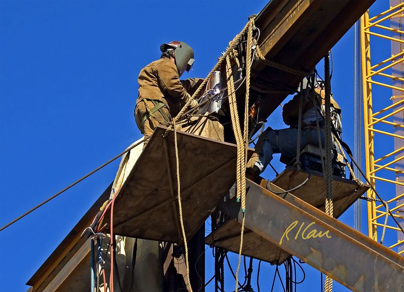 Steel construction: Two leather clad structural ironworkers perform torch work on massive steel connection of large steel truss. Each is working off of a rope supported plywood temporary work platform about 50 ft in the air. Each ironworker has fall protection from body harness, safety lanyard, and tie off to top chord of steel truss independent of the work platform. Ironworkers working at height on a small temporary platform in the dark behind welding masks are in an extremely vulnerable situation that requires secure fall protection. UCLA, Los Angeles, CA, 2004.
