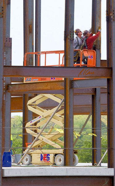 Structural ironworkers on JLG 2032E2 20 ft scissor lift guide crane supported structural steel wide flange column section into position to splice it to top of column below. Ashley Terrace, AnnArbor, Michigan, 2007