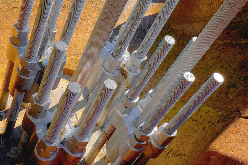 Steel/bridge/suspension/cable construction: Anchorage for steel wire cables of Palais de Justice pedestrian suspension bridge over the Saone River. Each suspension cable is anchored by four long threaded bolts embedded in concrete, inside a drilled hole in a large stone. Lyon, France September 2006