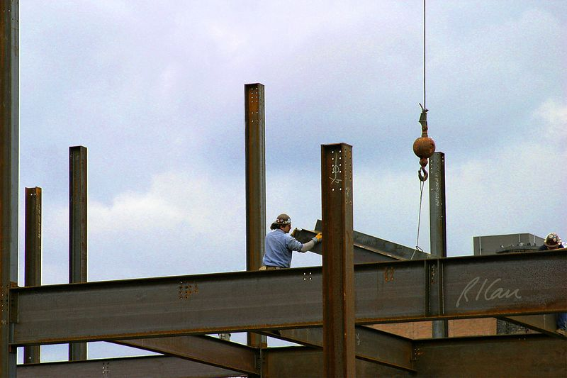 Structural steel construction: Ironworkers receive and set wide flange beam in erecting structural steel in construction of YMCA, Ann Arbor, 2004