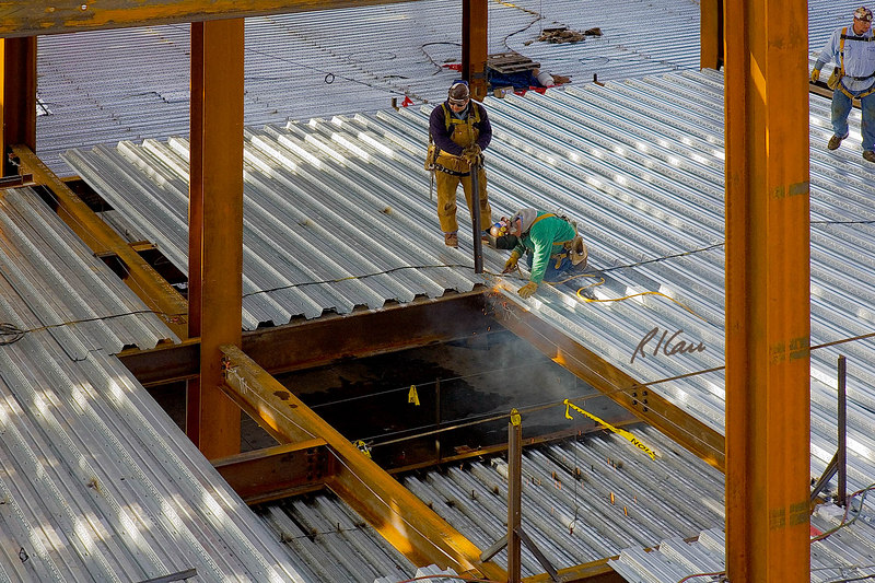 Structural steel ironworker arc welds corrugated steel deck to beams at periphery of floor opening. Standing ironworker is holding a steel angle iron to be welded in corner to provide support for perimeter cable fall protection (see the other two corners). Ross School of Business, University of Michigan, Ann Arbor. January, 2007.