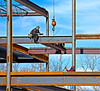 Steel construction/erection: Ironworker standing on girder near photo bottom tosses erection bolts to ironworker straddling girder above, for him to use in erecting beam(s) on opposite side of girder. Two bolts sit on top of girder flange, and third is mid air (see arrow to it from circled, slightly enlarged guide), with ironworkers hands waiting to grasp it. Ironworker standing on lower girder has no fall protection, and he is tossing bolts with the hand he would use to hold on to column. Depot Street, Ann Arbor, Michigan on a cold, windy day in February 2006.