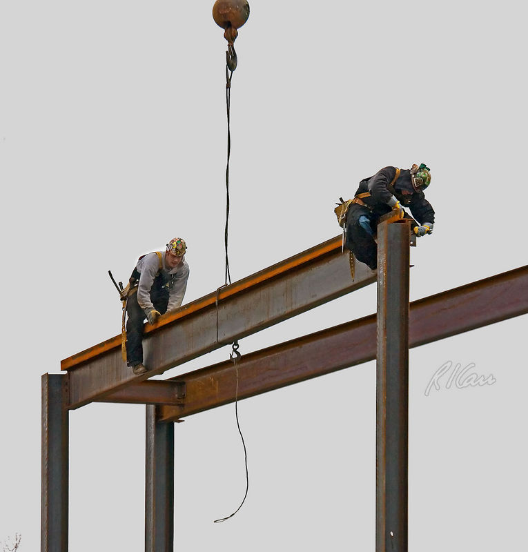 Steel construction/erection: Crane supports center of steel girder as two erection ironworkers erect structural steel using temporary bolts. Ironworker on right is sitting on end of girder/beam, using the pointed end of his spud wrench to pry end of beam into position to connect punched holes in girder and column. Ironworker on left has just cooned out (walked out with feet on lower flange on either side of girder) to near center of girder, at which point he will release girder from cable sling after his partner on right has secured support of girder by the column. The far end of girder is supported by temporary bolt(s) connecting girder to column. After structural steel frame has been erected with temporary bolts, the entire frame will be plumbed up, section by section, and permanent bolts will be installed. Depot Street, Ann Arbor, Michigan, February 2006.