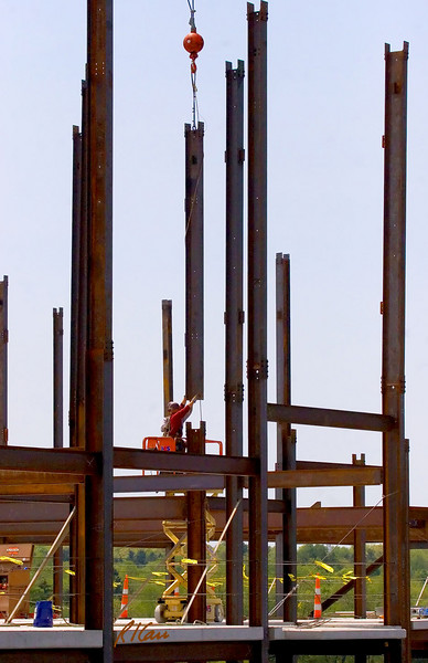 Structural ironworkers on scissor lift guide crane supported structural steel wide flange column section into position to splice it to top of column below. Ashley Terrace, Ann Arbor, Michigan April, 2007.